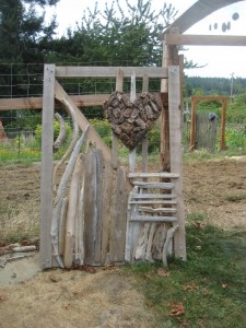 Driftwood designs and a bark heart adorns the garden gate.